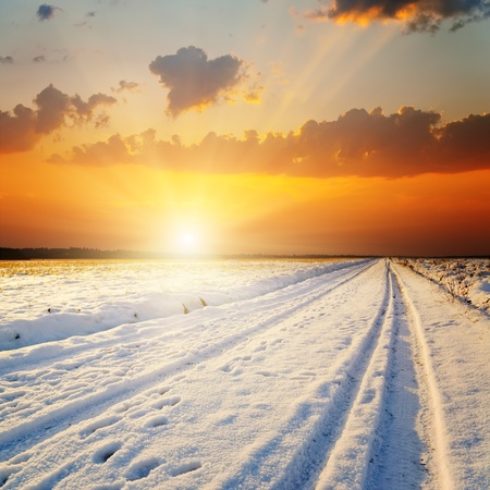 sunrays: winter landscape. sunset over road with snow