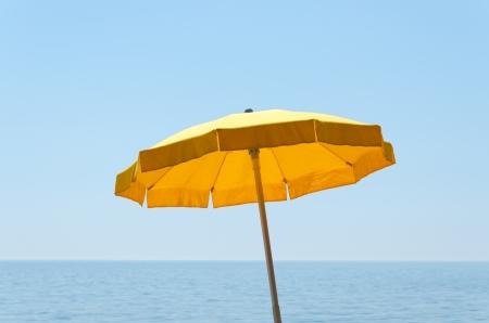yellow umbrella: yellow umbrella over sea under blue sky Stock Photo