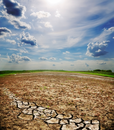 dramatic sky over dry cracked earth photo