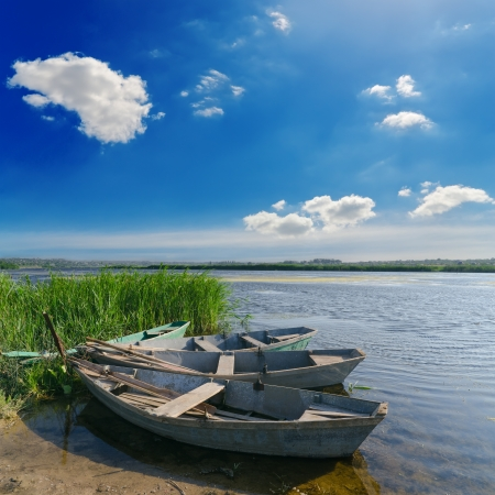 rowboat: beautiful river and old boats near green grass under cloudy sky Stock Photo