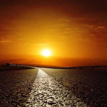 アスファルトの道路に赤い夕日