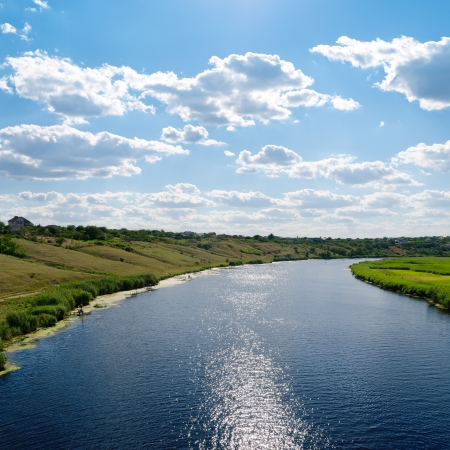 flowing river: view to river with reflections and blue cloudy sky
