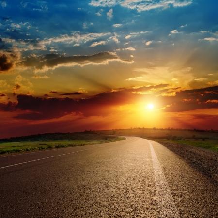 beautiful sunset over asphalt road photo