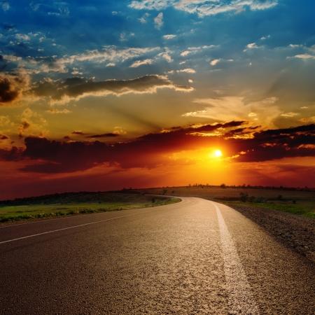 puesta de sol: rojo atardecer espectacular en la carretera de asfalto