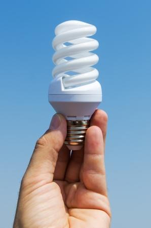 low energy: energy saving lamp in hand