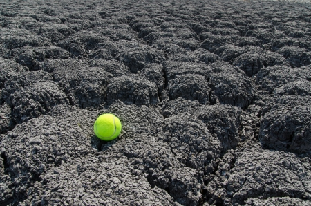 tennis ball on cracked land photo