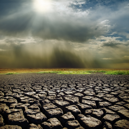 dramatic sky with sun over drought earth photo