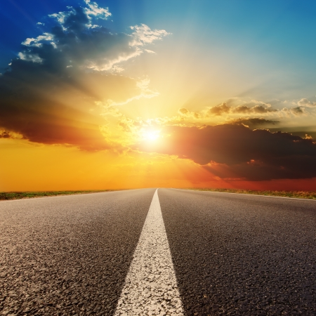 roadway: asphalt road under sunset with clouds Stock Photo