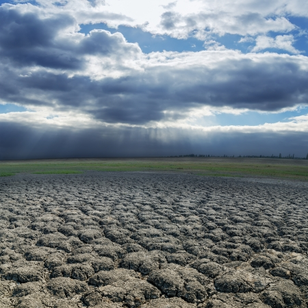 dramatic sky over drought earth photo