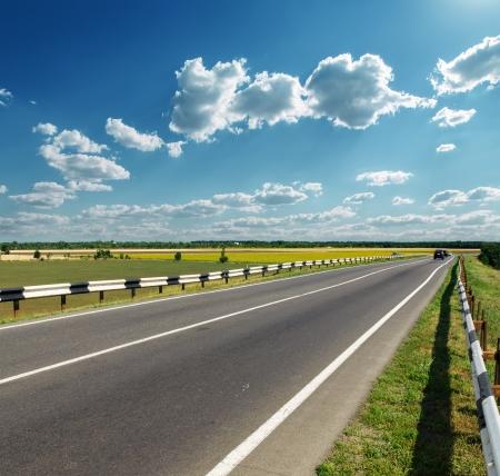 side road: asphalt road to horizon in cloudy sky