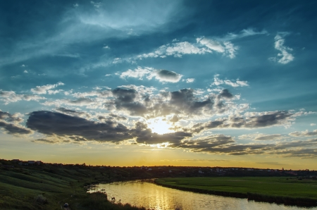 cloudy sunset over river photo
