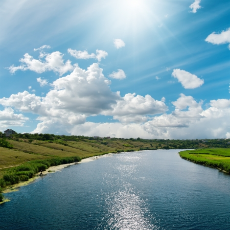river with reflections and blue cloudy sky