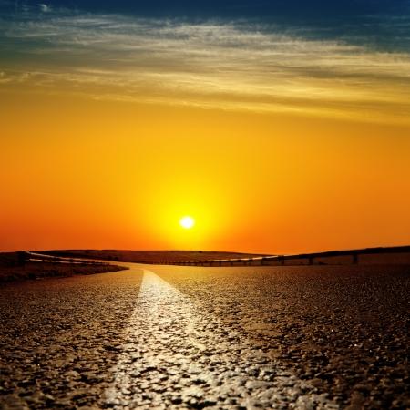 carretera de asfalto hasta el rojo atardecer Foto de archivo