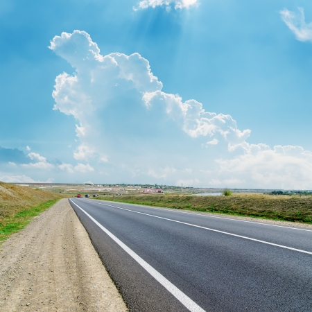 side road: asphalt road to cloudy horizon
