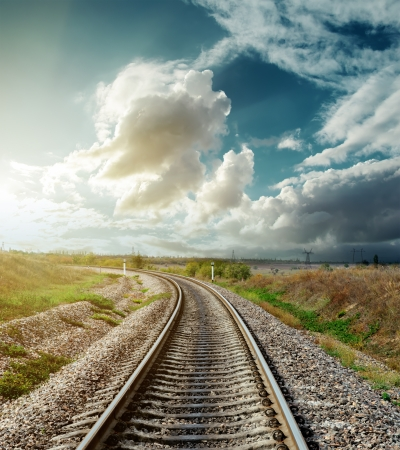 end of a long day: railway to horizon in sunset Stock Photo