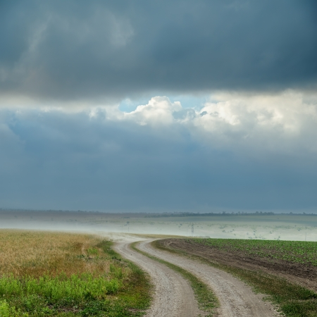 dirt road with dust under dark clouds. rain before photo