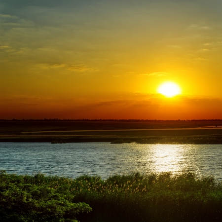 evening glow: dramatic sunset over river Stock Photo