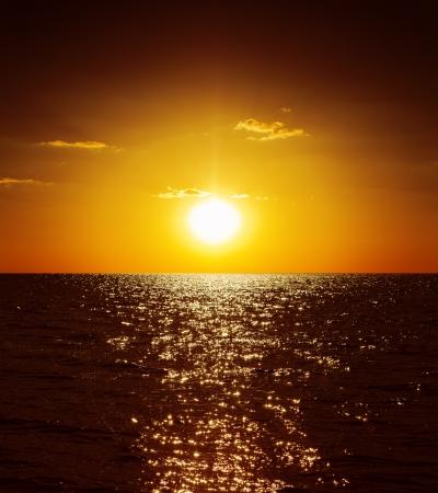 暗い水の上の黄金の夕日