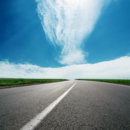 asphalt road to cloudy horizon in blue sky