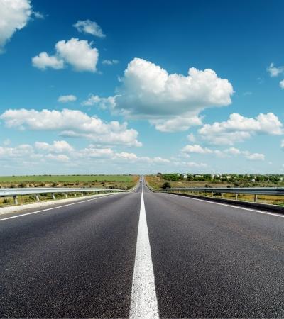 long road: black asphalt road to horizon under deep blue cloudy sky Stock Photo