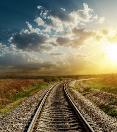 sun track: railroad goes to horizon in sunset Stock Photo