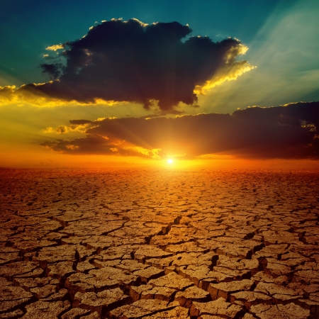 dramatic sunset over drought earth photo