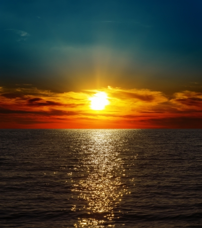 horizon over water: dramatic sunset over dark water Stock Photo