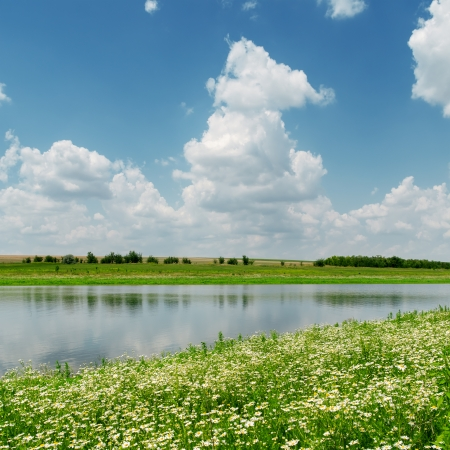 blue sky with clouds over river and meadow with chamomiles photo