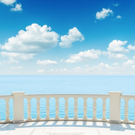 balcony view: view to the sea from a balcony under cloudy sky