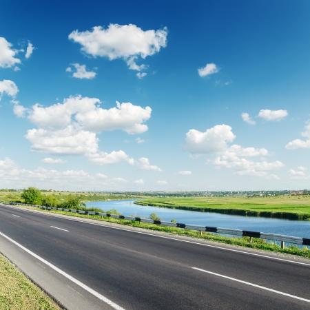 aspalt road near river under cloudy sky 스톡 콘텐츠