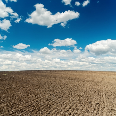plowed field and deep blue sky with clouds over it