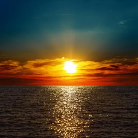 red dramatic sunset over darken sea