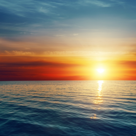 horizon reflection: good red sunset over darken sea Stock Photo