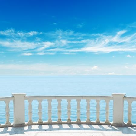 曇り空の下でバルコニー付きのテラスから海を見る