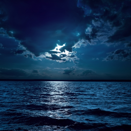 over the moon: moon light over darken water in night