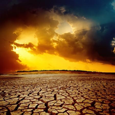 calentamiento global: puesta de sol sobre el desierto agrietado