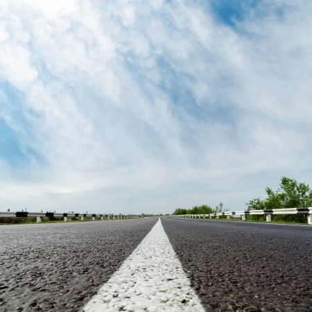 side road: white line on asphalt road and clouds over it