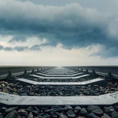 railway track: railroad closeup goes to horizon in dramatic sky Stock Photo