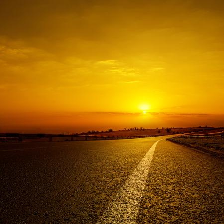 dramatic sunrise: asphalt road to orange horizon in sunset