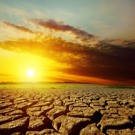 red clay: dramatic sunset over drought earth Stock Photo