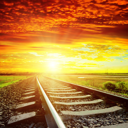 sunset with red clouds and railroad to horizon photo