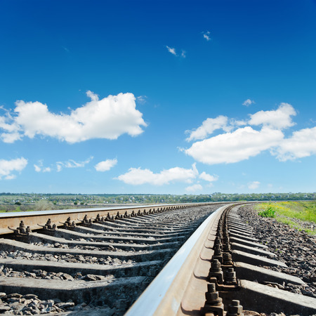 railroad to horizon under blue cloudy sky photo
