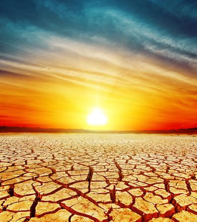 ひびの入った砂漠の上の黄金の夕日