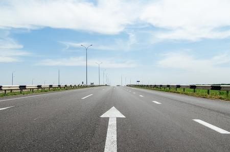 single lane road: white arrow on asphalt road Stock Photo