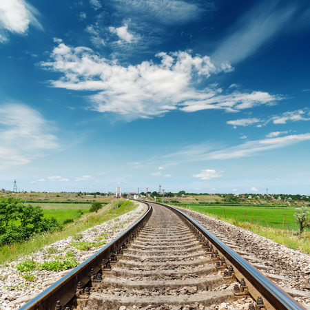 train tracks: rail road to horizon under deep blue sky