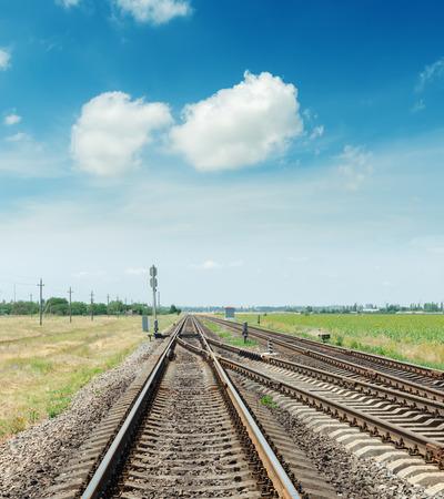 paesaggio industriale: incrocio di due linee ferroviarie e cielo blu con nuvole