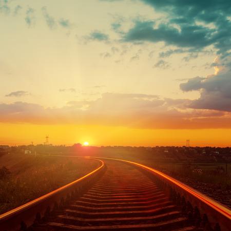 train tracks: good orange sunset over railroad to horizon