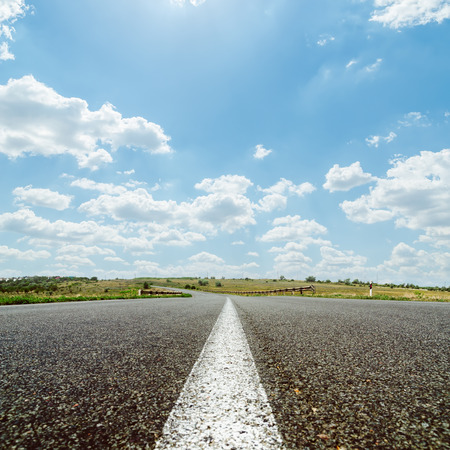 white line on asphalt road under sky with sun and clouds photo