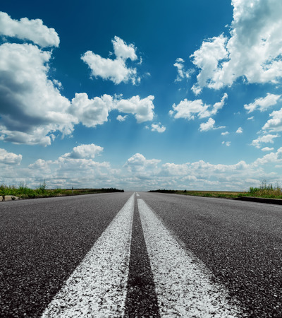 road texture: two white lines on black road and dramatic sky with clouds over it Stock Photo