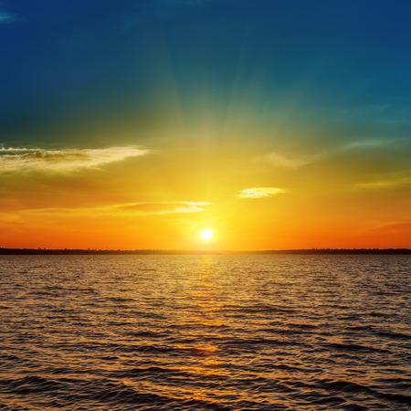 sunrise lake: orange sunset over dark water